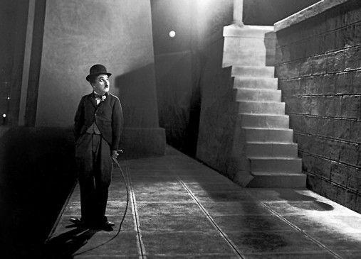 Der Tramp (Charlie Chaplin) blickt auf zu den Lichtern der Groflstadt