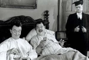 Ha, der Typ will auch in unser Bett! Oliver Hardy  (M.) und Stan Laurel (l.) amüsieren sich
