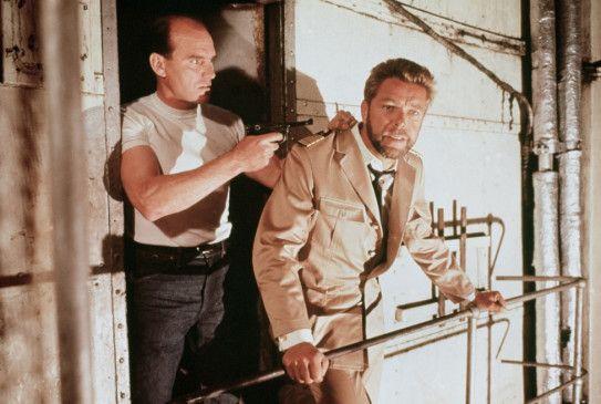 Kapitän von Koltze (Heinz Drache, r.) wird von den eigenen Leuten bedroht