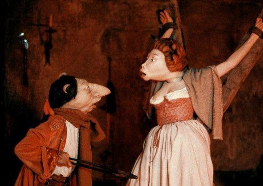Kerkermeister Ambert (Gabrielle van Damme) verhört die junge Kuh Justine in Marquis' Nachbarzelle