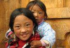 Auch mit kleinen Dingen glücklich: Mädchen mit Kleinkind in Bhutan