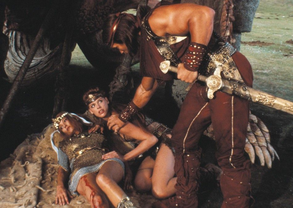 Komm, wir müssen hier weg! Kalidor (Arnold Schwarzenegger) mit Red Sonja (Brigitte Nielsen, M.)