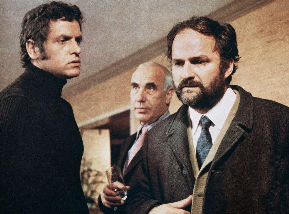 KGB-Mann Vladimir Monerow (Charles Regnier, M.) zwingt Roland (Paul Neuhaus, l.), seine Geschichte nicht zu veröffentlichen