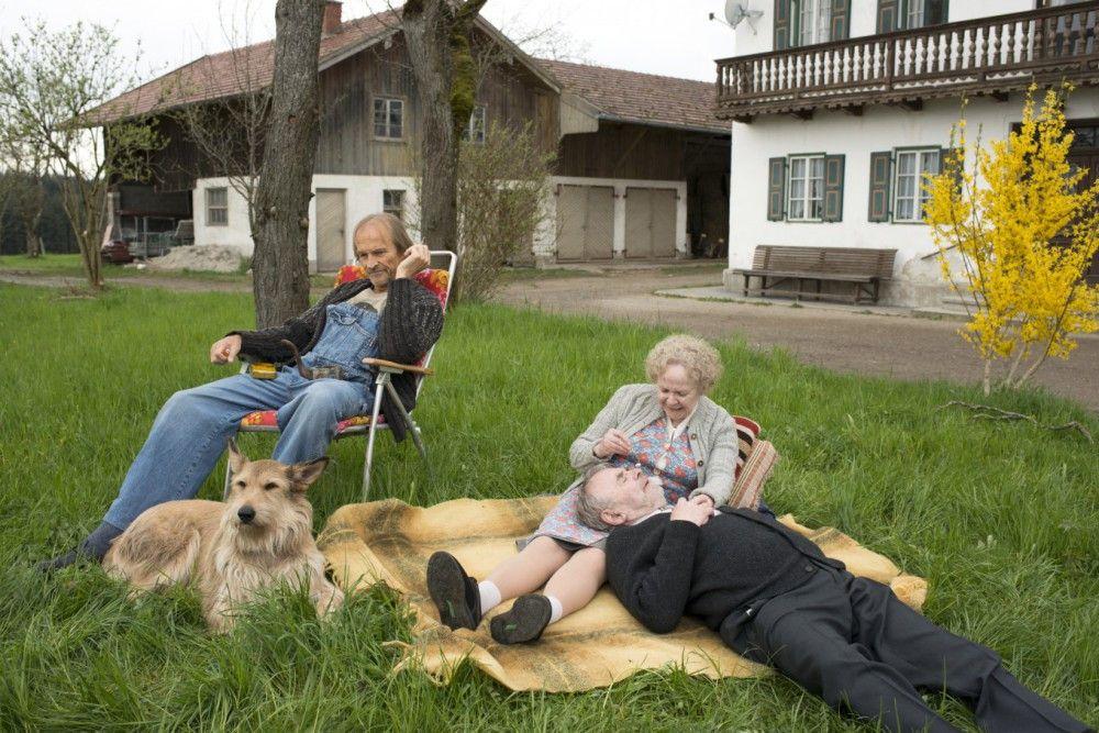 Eine neue Form der Idylle im Hause Eberhofer: Der Papa (Eisi Gulp, links), Hund Ludwig, die Oma (Enzi Fuchs) und ihre Jugendliebe Paul (Branko Samarovski) vertreiben sich die Zeit im Gras.