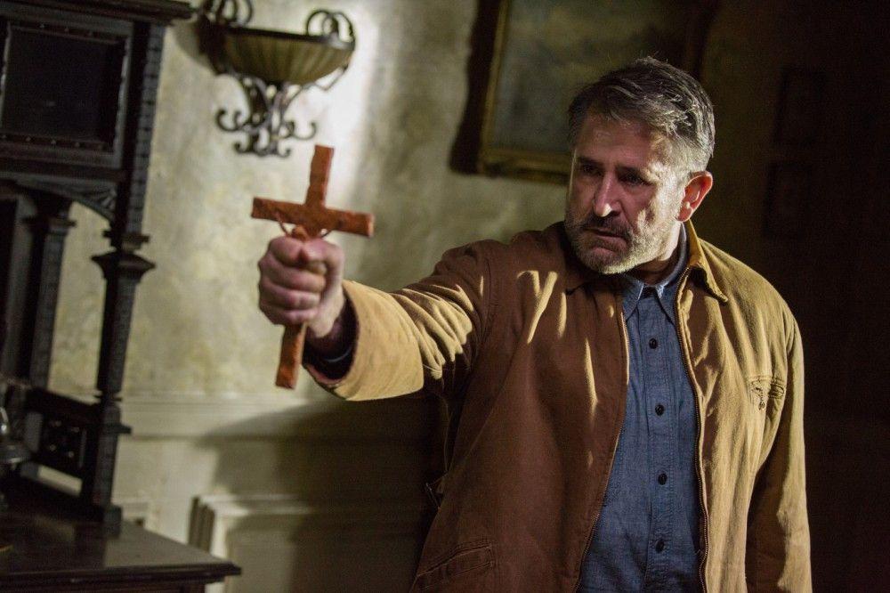 Gastgeber Samuel Mullins (Anthony LaPaglia) versucht der bösen Macht mit dem Kruzifix beizukommen.