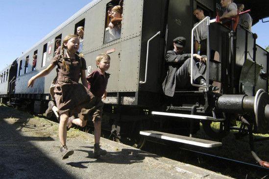 Die Wolfskinder Waltraud (Amber Bongard) und Ulrich Liedke (Lukas Schust) springen auf einen vorbeifahrenden Zug auf
