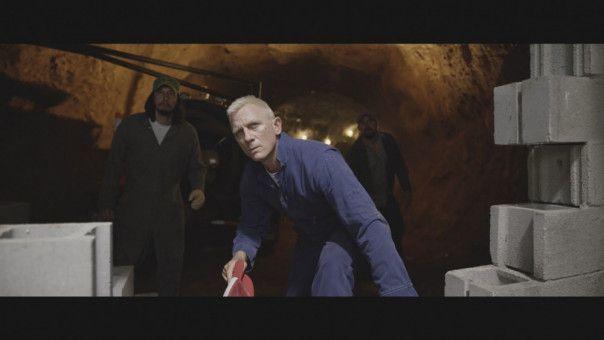 Sprengmeister Joe Bang (Daniel Craig, Mitte) sprengt den Tresor auf sehr ungewöhnlich-komische Art.