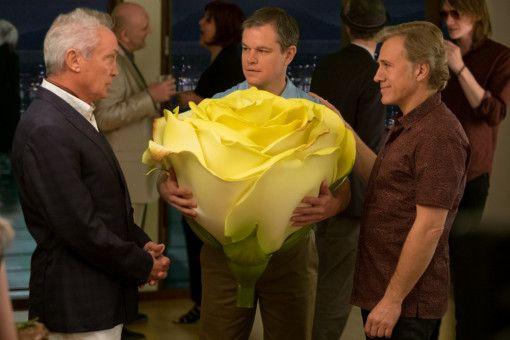 Mit einer Rosenblüte in Originalgröße ist Paul Safranek (Matt Damon, Mitte) der Star auf einer Party der Lebemänner Konrad (Udo Kier, links) und Dusan Mirkovic (Christoph Waltz).