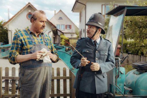 Wachtmeister Grimm (Erich Bock, rechts) beschwert sich bei Papa Moll (Stefan Kurt) über den Spielzeugpfeil, der ihn getroffen hat.