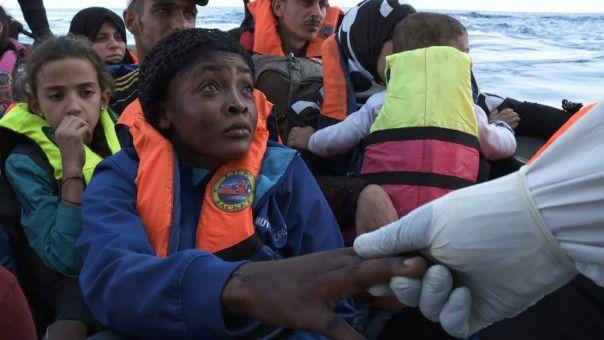 """Helfer auf der """"Mare Nostrum"""" geleiten die Flüchtlinge auf den riesigen Rettungskreuzer."""