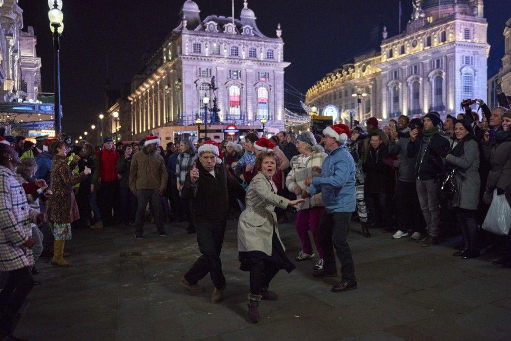 Bei einem Flashmob für einen wohltätigen Zweck am Piccadilly Circus begeistert die Tanztruppe von Sandra (Imelda Staunton) und Charlie (Timothy Spall) mit ihren Darbietungen die Menge.