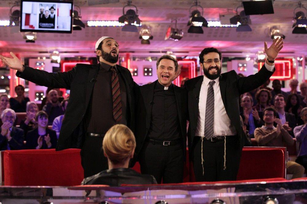 Auch das Fernsehen interessiert sich lebhaft für die Sakro-Pop-Barden Moncef (Ramzy Bedia, links), Benoit (Guillaume de Tonquédec, Mitte) und Samuel (Jonathan Cohen).