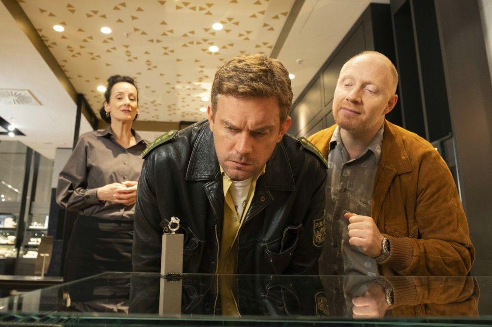 Franz Eberhofer (Sebastian Bezzel, Mitte) wird beim Kauf eines Verlobungsrings von Rudi (Simon Schwarz) und der Verkäuferin (Viola van der Burg) beraten.