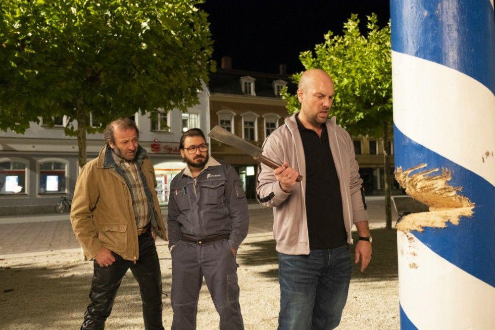 Wolfi (Max Schmidt, links), Flötzinger (Daniel Christensen, Mitte) und Simmerl (Stephan Zinner) machen sich über den Maibaum her - mit Erfolg.