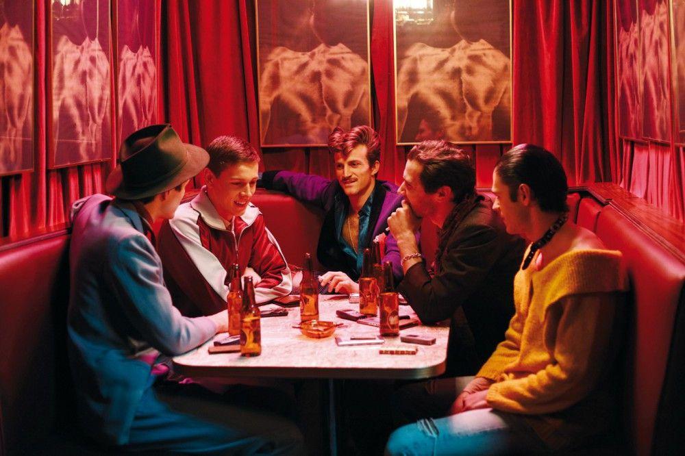 """David (Jonah Hauer-King, links), Victor (Raphael Desprez, Mitte) und die anderen männlichen Edelprostituierten nehmen Jim (Harris Dickinson, zweiter von links) in ihre Gruppe der """"Raconteurs"""" auf."""