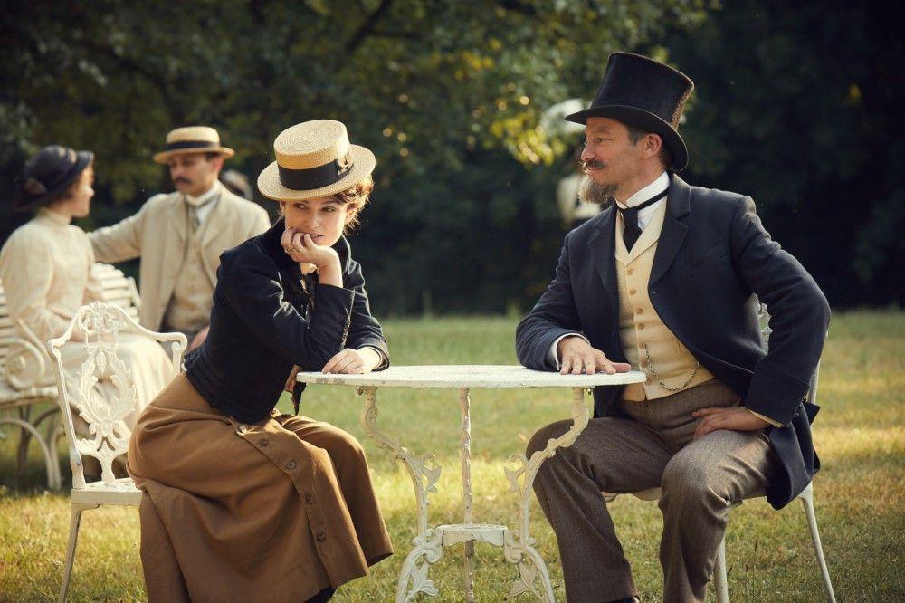 """Colette (Keira Knightley) und ihr Mann Willy (Dominic West) überlegen, wie viele Damen um sie herum im Park """"Claudine in der Schule"""" bereits gelesen haben oder es noch tun werden."""