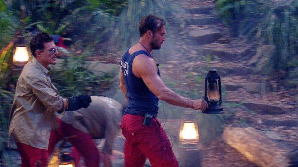 """Bastian Yotta bringt eine Lampe aus dem Camp, auf der es sich eine Spinne gemütlich gemacht hat. Chris Töpperwien  muss tatenlos mitansehen, wie sein Rivale zum """"Helden"""" wird."""