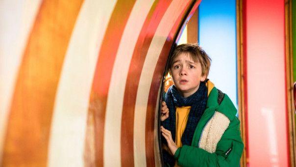 Frido (Luis Vorbach) versteckt sich auf dem Jahrmarkt vor seinen Eltern.