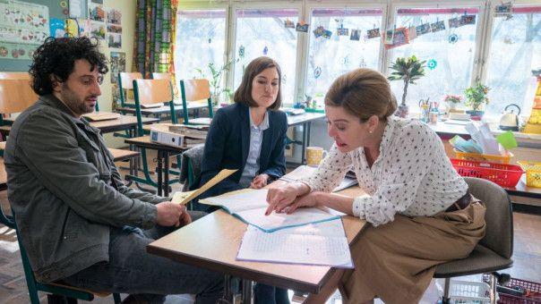 Fridos Eltern Gesa (Marie Leuenberger) und Michael (Serkan Kaya) werden von Fridos Lehrerin Frau Klawitter (Margarita Broich, rechts) über die schlechten Noten des Jungen informiert.
