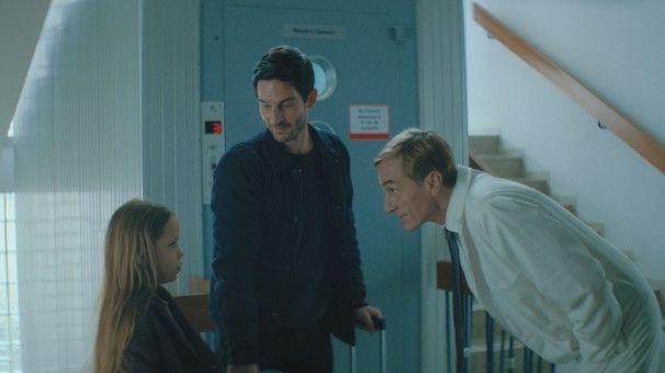 Die Atmosphäre in dem rumänischen Krankenhaus, in dem sie operiert werden soll, macht Jana (Maggie Valentina Salomon) Angst. Da helfen auch die Beruhigungsversuche ihres Vaters (Christoph Bach, Mitte) und des operierenden Arztes (André Hennicke) nichts.