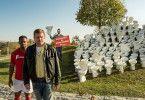 Flötzinger betreibt am Kreisverkehr Werbung. Franz Eberhofer (Sebastian Bezzel, rechts) und Buengo (Castro Dokyi Affum) wundern sich über diese Strategie.