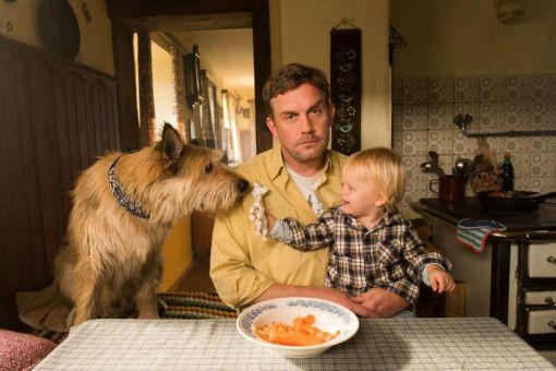 Vaterfreuden am Esstisch: Franz Eberhofer (Sebastian Bezzel, Mitte) mit Paul (Luis Sosnowski) und Hund Ludwig. Im Kino lebt er noch, in den Büchern hat der arme Hund inzwischen das Zeitliche gesegnet.