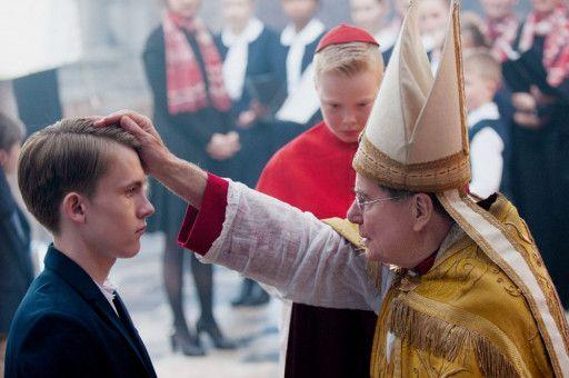 Lyons Erzbischof Barbarin (François Marthouret) hat die Verbrechen eines Priesters an Alexandre jahrelang verschwiegen und spendet dessen Sohn Gauthier (Max Libert) nun die Firmung.