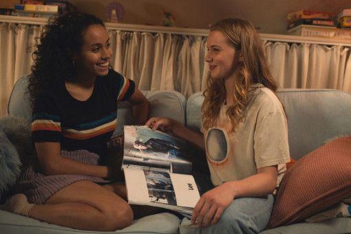 Vanessa (Kristin Hunold, links) zeigt ihre Freundin Jessica (Luna Wedler) Fotos von deren Model-Boyfriend.