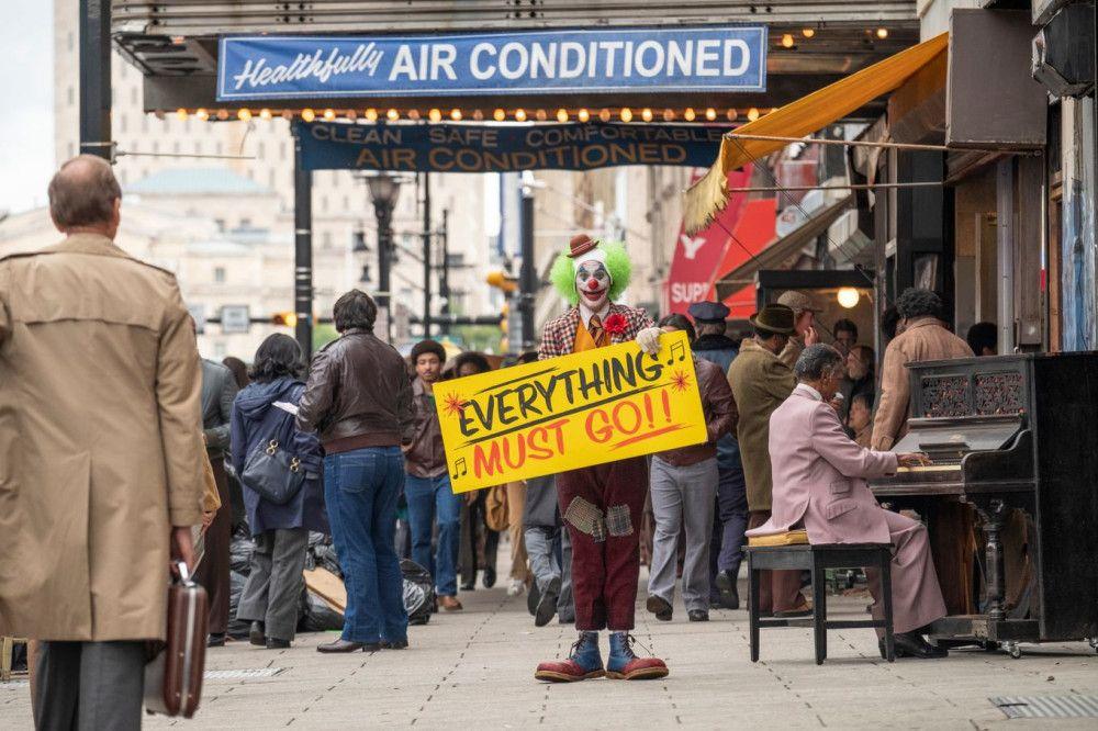 Auf den Straßen von Gotham City macht Clown Arthur (Joaquin Phoenix) Werbung für einen Schlussverkauf.
