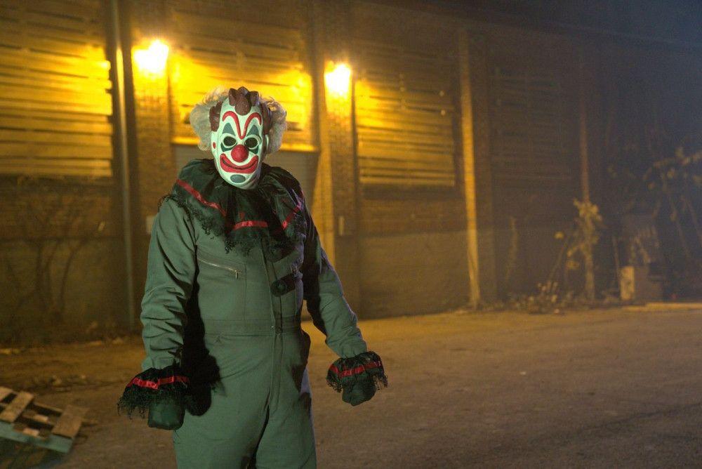 Ein stummer Clown begrüßt die Gruppe am Eingang der Spukhausattraktion.