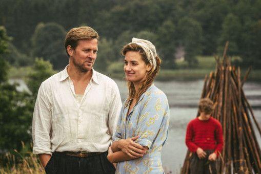 Familienaufstellung am Wasser: Tronds Vater (Tobias Santelmann) und die Mutter seines Freundes (Danica Curcic) sind im Gespräch vertieft, während der junge Trond (Jon Ranes, hinten) abseits steht.