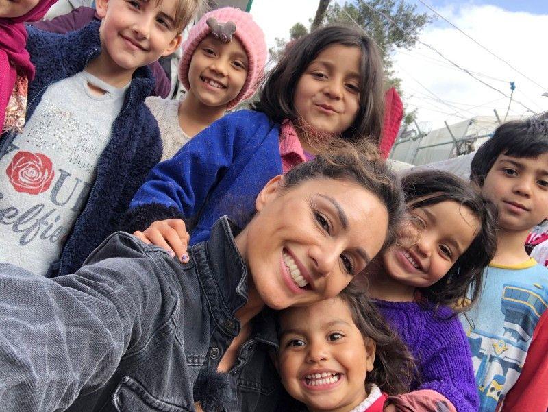 Nazan Eckes und einige Kinder aus dem Flüchtlingslager Moria lächeln für die Kamera.