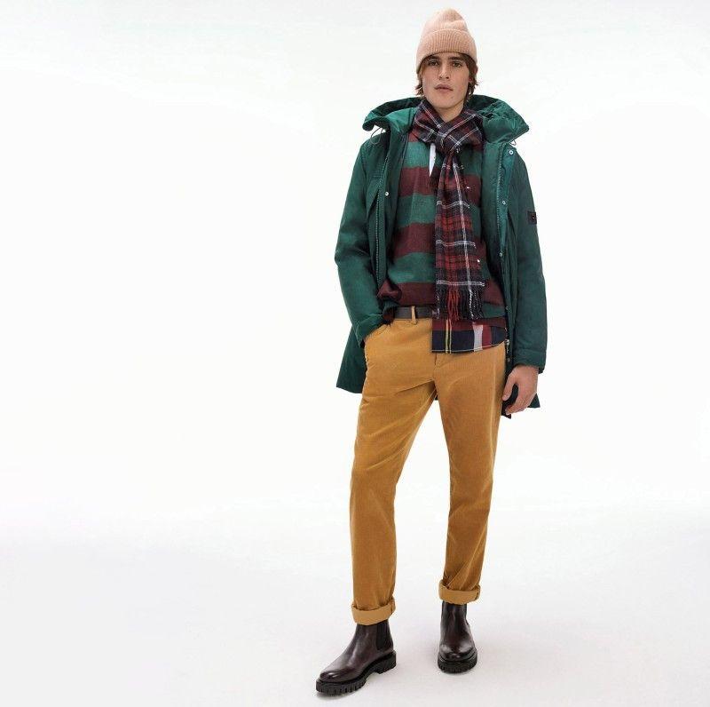 Leger trifft auf verspielt: Klassische Looks können auch durch eher ungewöhnliche Farbakzente aufgelockert werden. Bei Tommy Hilfiger geschieht das dezent, wie bei diesem Look mit ockerfarbener Hose und grüner Jacke.