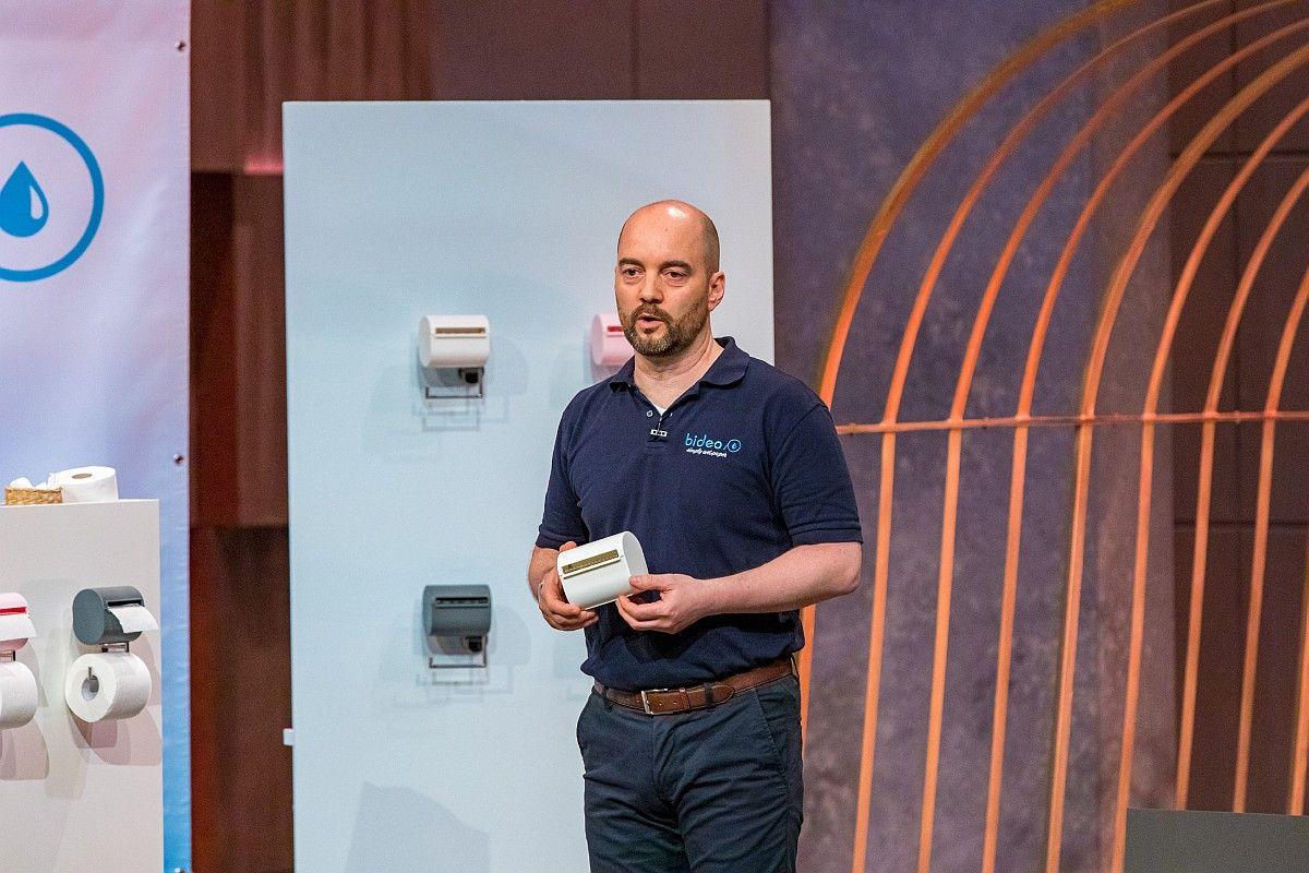 """<b>Folge 1:</b> Thorsten Homma hat """"bideo"""" entwickelt, einen Toilettenpapierbefeuchter vor. Er soll das Problem von Rohrverstopfungen und Umweltverschmutzung durch Feuchtpapier lösen. Ralf Dümmel holt sich 20 Prozent der Firmenanteile für 100.000 Euro."""