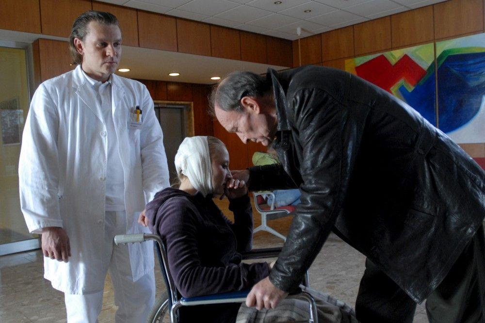 Hauptkommissar Hagen Dudek (Michael Mendl, r.) ist verzweifelt: Seine junge Mitarbeiterin Simone Westermann (Anna Maria Mühe, m.) ist durch eine Verletzung im Dienst an den Rollstuhl gefesselt. Der behandelnde Arzt (Christoph Tomanek, l.) macht beiden wenig Hoffnung auf Heilung.
