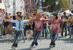 Sirtaki tanzende Cowboys in München: Nektarios (Adam Bousdoukos, r.) mit Ehemann Lambert (Heiner Lauterbach, m).