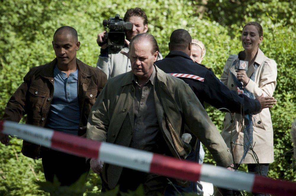 In einem Park in Amsterdam wird die grausam zugerichtete Leiche eines Jungen gefunden. Kommissar Bruno van Leeuwen (Peter Haber, r.) und sein Teamkollege Remko Vreeling (Patrick Abozen, l.) auf dem Weg zum Tatort. (Im Hintergrund: Unbekannte Kleindarsteller).