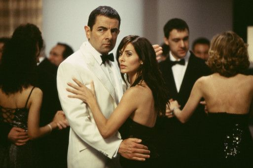 English (Rowan Atkinson) und Lorna (Natalie Imbruglia) belauern Sauvage (nicht im Bild) bei seiner großen Party.  (Andere Darsteller im Hintergrund nicht bekannt.)