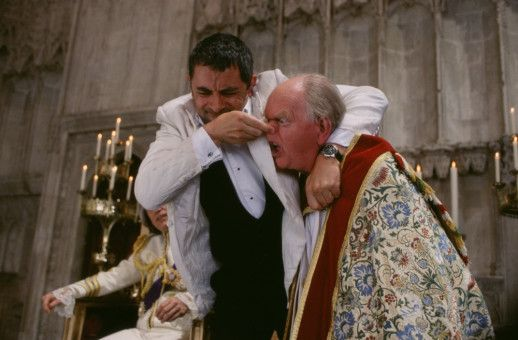 English (Rowan Atkinson; M.) glaubt nicht, dass der Erzbischof von Canterbury (Oliver Ford Davies, r.) der echte ist und unterzieht ihn einer schmerzhaften Überprüfung.  Sauvage (John Malkovich) sieht seine Krönung noch nicht in Gefahr.
