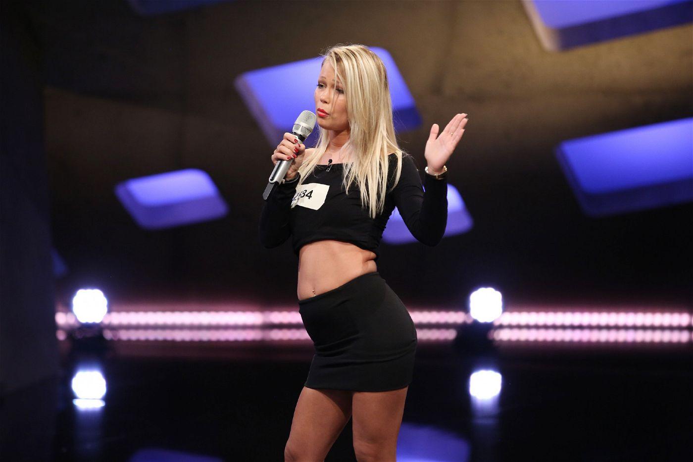 """Kitty Monroe, von Beruf """"Oben-Ohne-Moderatorin"""", präsentiert den Song """"Boom Boom Boomerang"""" von Blümchen."""