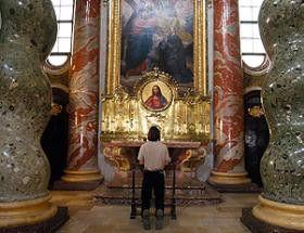 Ein Gläubiger in stiller Andacht vor dem Jesusbild