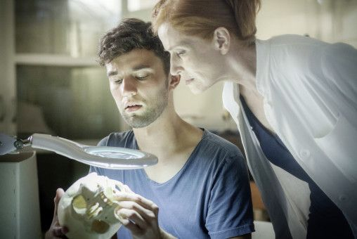 Der Doktorand Philip (Nils Strunk) zeigt Prof. Magdalena Mittlich (Sibylle Canonica) einen Schädel.