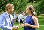 Während die Gäste (Komparsen, Hintergrund) die Verlobung von Julius Weber (Frederic Heidorn, l.) feiern, hat der vor seiner Verlobten ein Geheimnis, von dem Carla Schmitt (Dagny Dewath, r.) weiß.