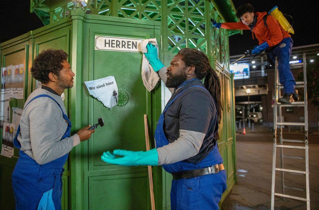 Ezequiel (Tyron Ricketts, li.) will nicht die Arbeit machen, die Reynaldo (Komi Mizrajim Togbonou, re.) von ihm verlangt – und zwar die öffentlichen Toiletten reinigen.