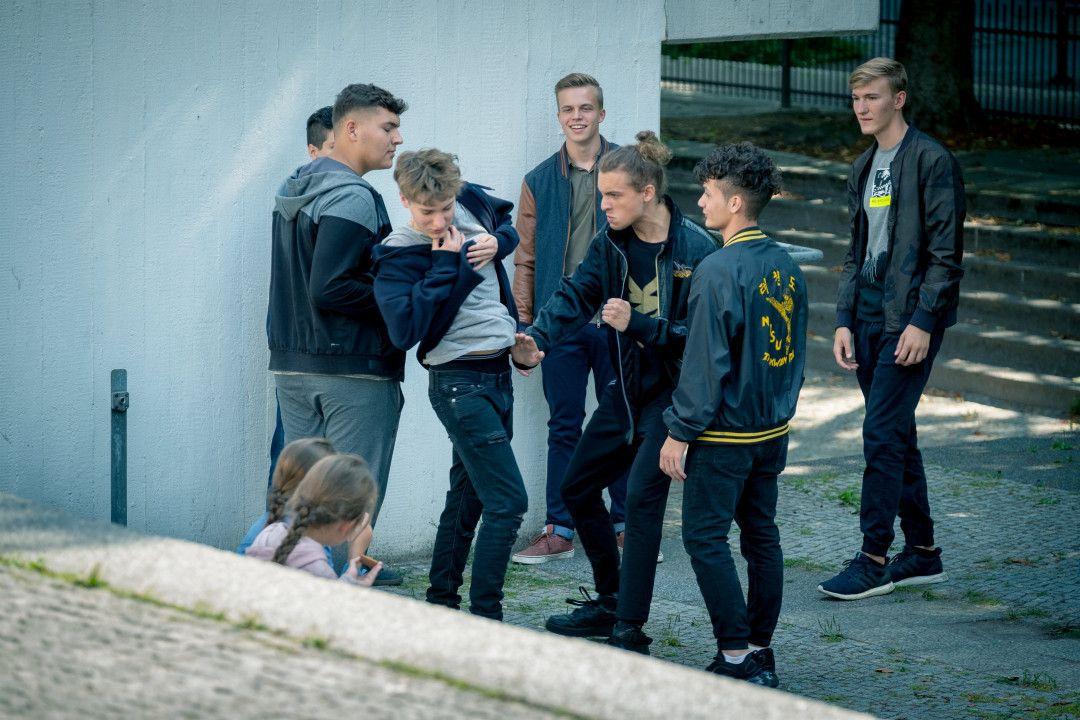 Annika (Anna Brüggemann) sieht, wie Karim (Oskar Redfern, r.) Max (Samuel Benito, l.) auf dem Schulhof die Kette vom Hals reißt, greift aber nicht ein.