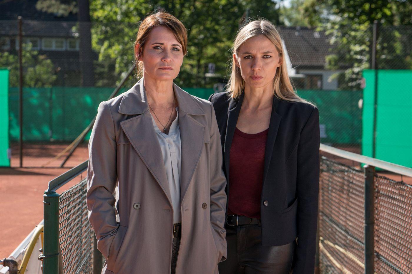 Maike (Anja Kling, l.) und Pia (Annika Blendl, r.) finden Hausbesitzer Krampe mit Britta Zuber auf dem Tennisplatz.
