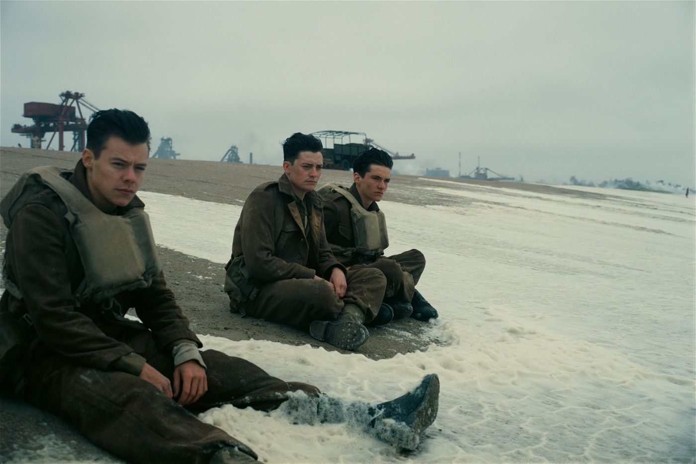 Nachdem ein Torpedo ihr Schiff zum Kentern brachte, sind Alex (Harry Styles, l.), Gibson (Aneurin Barnard, M.) und Tommy (Fionn Whitehead, r.) wieder zurück am Strand von Dünkirchen.