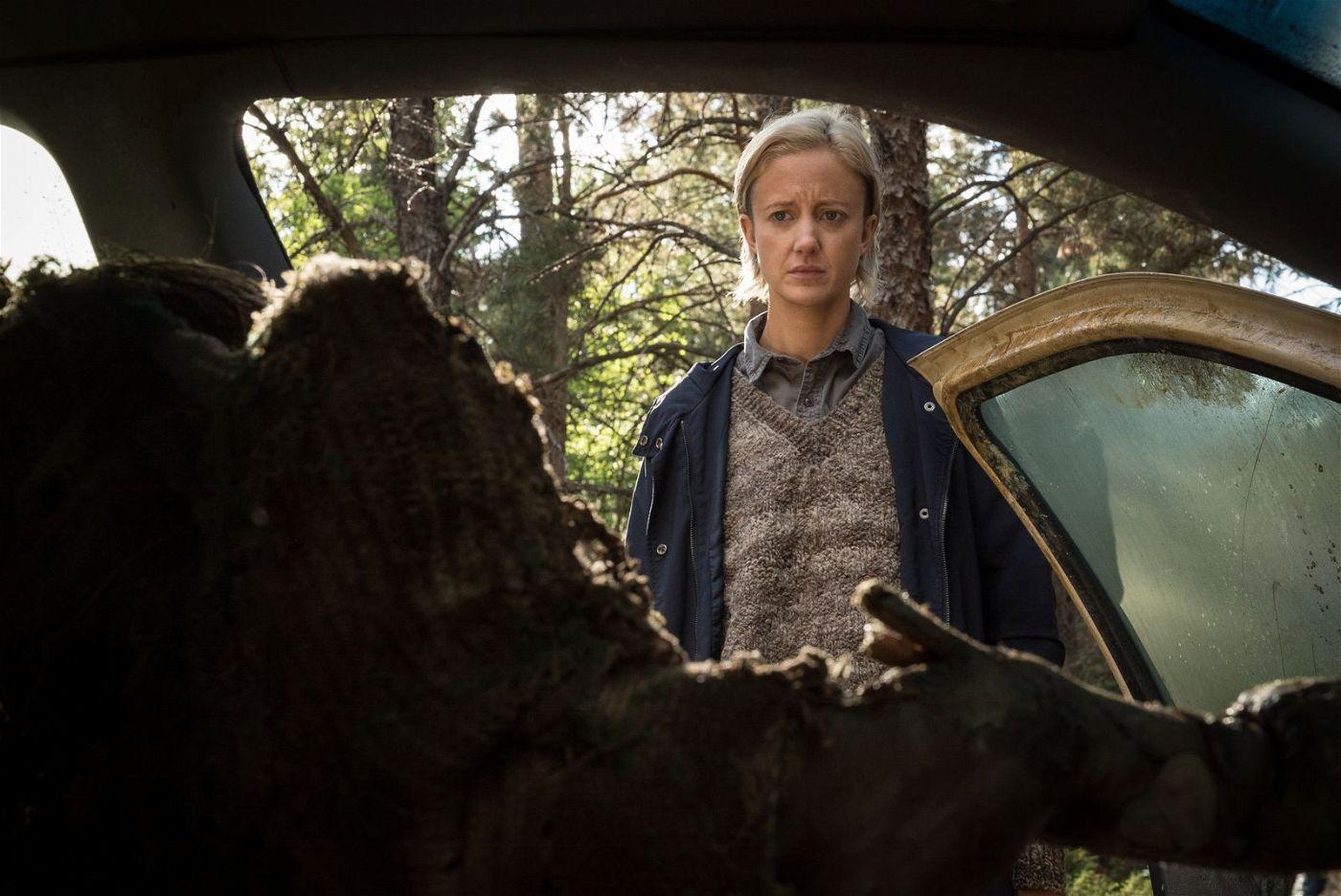 Muldoon (Andrea Riseborough) begutachet die stark verweste Leiche einer verunglückten Autofahrerin und erhält erste Hinweise auf das verfluchte Haus.