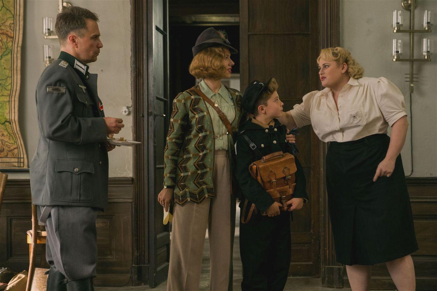 Fräulein Rahm (Rebel Wilson, rechts) und Hauptmann Klenzendorf (Sam Rockwell, links) nehmen Jojo (Roman Griffin Davis) unter ihre Fittiche. Jojos Mutter Rosie (Scarlett Johansson) passt das gar nicht.