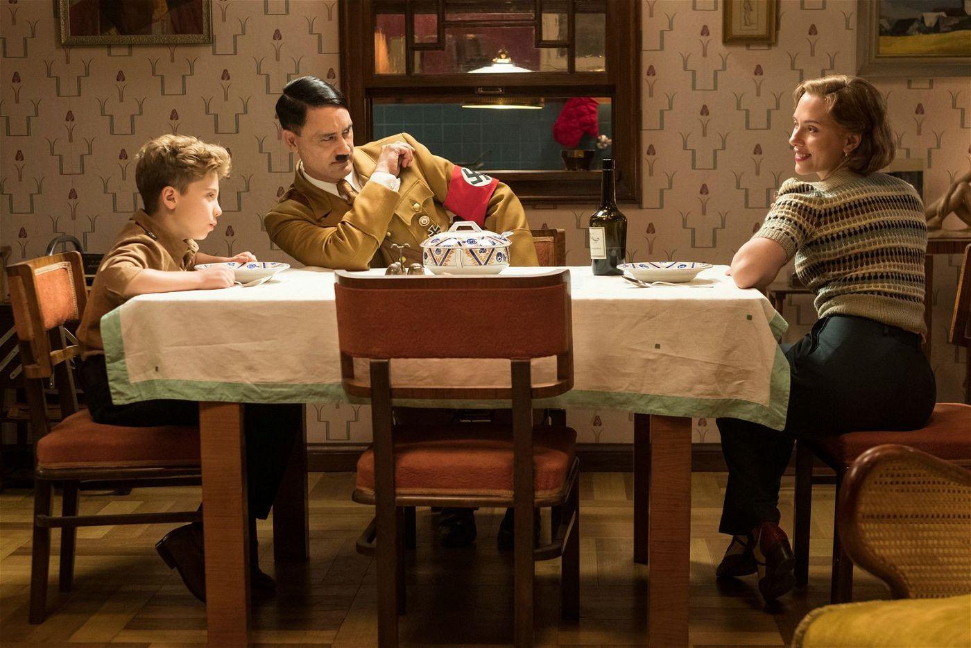 Mit Hitler (Taika Waititi, Mitte) bei Tisch: Jojos Mutter (Scarlett Johansson) weiß nicht, dass ihr Sohn (Roman Griffin Davis) einen imaginären Freund hat.